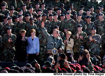 "Surrounded by cheering soldiers at Fort Campbell, Kentucky, <a href=""/news/releases/2001/11/20011121-3.html"">President George W. Bush</a> addressed the troops and shared a turkey dinner with them Nov. 21. ""More than 3,000 soldiers from this post have been deployed to Kosovo for six-month rotations,"" said the President. ""They kept supplies away from rebels in Macedonia, made the recent election in Kosovo possible. I'm glad to report that all of them from this base will be home by Thanksgiving."". White House photo by Tina Hager."