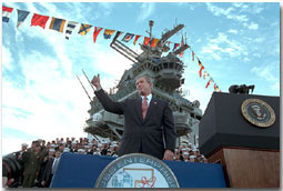 "President George W. Bush salutes during his remarks at the USS Enterprise Dec. 7.  ""I'm grateful for this warm welcome on the deck of the ""Big E,"" said the President. ""America is proud of this fine carrier and we're really proud of her crew.  You're serving at a crucial moment for the cause of peace and freedom, and your country thanks you.""White House photo by Paul Morse."