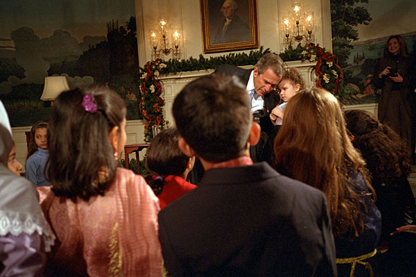 "President George W. Bush takes a small break to hear what Alexandria Hudome, 3, has to say as he reads a poem to Muslim children during Eid Al-Fitr at the White House December 17, 2001. ""Eid is a time of joy, after a season of fasting and prayer and reflection,"" said President Bush. ""Each year, the end of Ramadan means celebration and thanksgiving for millions of Americans."" White House photo by Tina Hager."