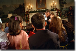 "President George W. Bush takes a small break hear to what Alexandria Hudome, 3, has to say as he reads a poem to Muslim children during Eid Al-Fitr at the White House December 17, 2001. ""Eid is a time of joy, after a season of fasting and prayer and reflection,"" said President Bush. ""Each year, the end of Ramadan means celebration and thanksgiving for millions of Americans."" White House photo by Tina Hager."
