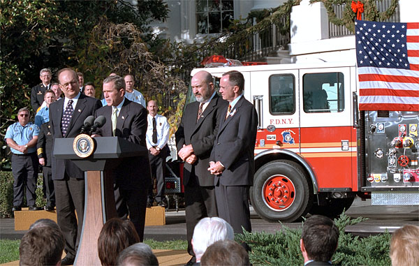 "Accompanied by firemen and other distinguished guests, President George W. Bush speaks during a ceremony held to honor the gift of a new firetruck for city of New York on the South Lawn Dec. 19. Donated by the state of Louisiana, the ""Spirit of Louisiana,"" will replace one of the 35 firetrucks that were destroyed in the Sept. 11 attacks. Standing with the President is Ronald Goldman, (left) Louisiana Governor Mike Foster, (center) and Louisiana Representative Hunt Downer. White House photo by Tina Hager."