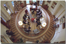 President George W. Bush hosts a meeting in the Oval Office decorated with the new presidential rug on December 20, 2001. The rug, which is unique to the Bush administration, arrived earlier in the week and was unveiled to the media on Friday December 21, 2001. Members from the Office of Homeland Security and other White House staff attended the meeting. The participants included (clockwise from the bottom), President George W. Bush, Governor Tom Ridge, Dr. Condoleezza Rice, Admiral Steve Abbot, Karen Hughes, Dean McGrath, Karl Rove, Albert Hawkins, Mitch Daniels, Josh Bolton, and Andy Card. White House Photographer Paul Morse is at left. White House photo by Paul Morse.