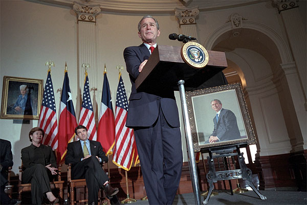As Mrs. Bush and Texas Governor Rick Perry listen, President George W. Bush speaks during the ceremony for the unveiling of his portrait painted by Scott Gentling at the Texas State Capitol in Austin Jan. 4, 2001. White House photo by Eric Draper.
