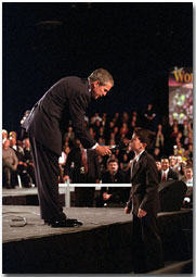 President George W. Bush holds the microphone for a boy during a town hall meeting in Ontario, Calif., Jan. 5. The President spoke about and listened to comments concerning the economy, immigration and the war in Afghanistan. White House photo by Eric Draper.