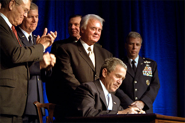 President George W. Bush signs a defense appropriations bill at the Pentagon, Jan., 10. Photographed with President Bush are Secretary of Defense Donald Rumsfeld (far left), Chairman of the Joint Chiefs of Staff General Richard Myers (center, left), House Armed Services Committee Chairman Rep. Bill Young (directly behind President Bush), Army Vice Chief of Staff Gen. John Keane (behind Mr. Young) and Air Force Vice Chief of Staff General Robert H. Foglesong (far right). White House photo by Paul Morse.