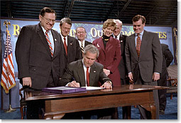 President George W. Bush signs the Small Business Liability Relief and Brownfields Revitalization Act in Conshohocken, Pennsylvania, Jan. 11. Standing left to right and Rep. Paul Gillmor of Ohio, Rep. Robert Borski of Penn., State Attorney General Mike Fisher, EPA Administrator Christie Todd Whitman, Rep. Joseph Hoeffel of Penn. and Pennsylvania Governor Mark Schweiker. White House photo by Eric Draper.