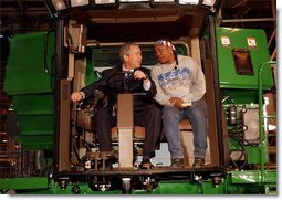 "President George W. Bush talks with assembly worker Deborah Davis after starting up a combine with a gold-plated ignition key at John Deere Harvester Works in East Moline, Ill., Monday, Jan. 14, 2002. ""I'm confident in the American farmer,"" said the President, addressing about 1500 employees and supporters. ""I know the American farmer is more efficient, and can raise more crop than anybody, anywhere in the world.""  White House photo by Eric Draper"