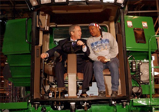 "President George W. Bush talks with assembly worker Deborah Davis after starting up a combine with a gold-plated ignition key at John Deere Harvester Works in East Moline, Ill., Monday, Jan. 14, 2002. ""I'm confident in the American farmer,"" said the President, addressing about 1500 employees and supporters. ""I know the American farmer is more efficient, and can raise more crop than anybody, anywhere in the world."" White House photo by Eric Draper."