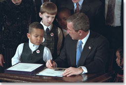 "With the help from some new friends, President George W. Bush signs legislation promoting safe and stable families at the White House Jan. 17, 2002. ""The legislation reaffirms our country's commitment to helping children grow up in secure and loving families by encouraging adoption,"" said the President during the ceremony. White House photo by Paul Morse."