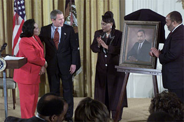 Proclaiming a holiday in honor of Martin Luther King, Jr., President George W. Bush receives a portrait of the civil rights leader from his wife and children in the East Room Jan. 21, 2002. Photographed from left to right are Coretta Scott King, the President, Rev. Bernice King and Martin Luther King III. WHITE HOUSE PHOTO BY TINA HAGER.