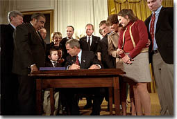 "President George W. Bush looks over to Thomas Martello, 6, during the signing ceremony of the Victims of Terrorism Tax Relief Act in the East Room Jan. 23. ""We're joined today by families who have lost loved ones in the great acts of evil,"" said the President. ""As you draw on faith and personal strength to cope with your grief, I hope you'll also find comfort in the knowledge that your nation stands with you and prays for you. We mourn those whom we've lost, and we face the future together."" White House photo by Eric Draper."