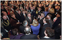 President George W. Bush wades into a crowd of handshakes and flashing cameras as he welcomes mayors and county official to the East Room Jan. 24. White House photo by Tina Hager.