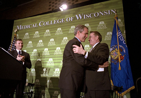 President George W. Bush embraces Secretary of Health and Human Services and former Wisconsin Governor Tommy Thompson after speaking about healthcare reform issues at the Medical College of Wisconsin in Milwaukee, Wis., February 11, 2002. Wisconsin's current governor Scott McCallum is also pictured. White House photo by Paul Morse.