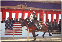 President George W. Bush, Mrs. Bush and their host Prime Minister Junichiro Koizumi watch a demonstration of horseback archery during a visit to the Meiji Shrine in Tokyo, Monday, Feb. 18, 2002. President Bush's trip to Japan is the first of three countries he is visiting during his tour through Asia. White House photo by Paul Morse.