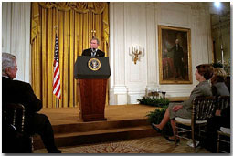 "President George W. Bush addresses the White House Conference on Preparing Tomorrow's Teachers in the East Room March 4, 2002. Pictured in the audience from left to right is U. S. Sen. Edward Kennedy (D-Mass.), Laura Bush and Lynne Cheney. ""We're focusing much of the teacher training effort on specific needs, like special education or math or science, and one of my passions, early reading,"" said the President. ""The Reading First program is aimed at making sure every child of every background can read by the third grade."" White House photo by Eric Draper."