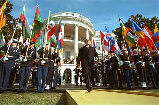 "Flying flags from countries contributing to the fight against terrorism, President George W. Bush approaches the podium on the six-month anniversary of the September 11th Attacks on the South Lawn. ""We have come together to mark a terrible day, to reaffirm a just and vital cause, and to thank the many nations that share our resolve and will share our common victory,"" said the President in his remarks. White House photo by Paul Morse."