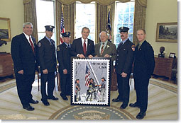 President George W. Bush stands for photos at the unveiling of the Postal Service's new stamp Commemorating the efforts of recovery workers in the aftermath from the attack upon the World Trade Center, President George W. Bush unveils a new stamp in the Oval Office March 11, 2002. Standing with the President from left to right are Postmaster General Jack Potter, Firefighter Bill Eisengrein, Firefighter George Johnson, Congressman Gary Ackerman, Firefighter Dan Williams and Photographer Thomas E. Franklin. White House photo by Tina Hager.