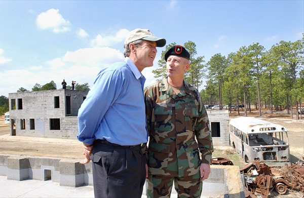President George W. Bush and Brigadier General Richard Mills, Deputy Commander of U.S. Special Forces, view a tactical demonstration from the roof of a building at Fort Bragg, North Carolina, Friday, March 15, 2002. White House photo by Eric Draper.