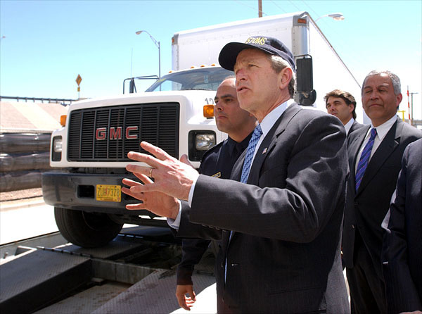 "President George W. Bush reviews the Vehicle and Cargo Inspection System during a tour of the cargo dock at the Bridge at the Americas in El Paso, Texas, Thursday, March 21. Also pictured, from left, are Port Operations Director David Longoria, Texas Governor Rick Perry and Congressman Henry Bonilla (R-23rd). ""I want this border to be modern; I want it to have the very best technology,"" said the President upon his arrival at the El Paso airport. ""I don't want it to be a neglected part of our country. I want it to be a place where we spend a lot of time and focus on it, so that it works the best it can possibly work."" White House photo by Eric Draper."