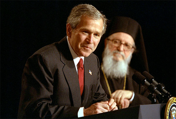 "Accompanied by His Eminence Archbishop Demetrios, Primate of Greek Orthodox Church of America, President George W. Bush addresses attendees of the Greek Independence Day Ceremony in the Eisenhower Executive Office Building March 25, 2002. ""America and Greece are strong allies, and we're strategic partners,"" said President Bush. ""Our nation has been inspired by Greek ideals, and enriched by Greek immigrants."" White House photo by Paul Morse."