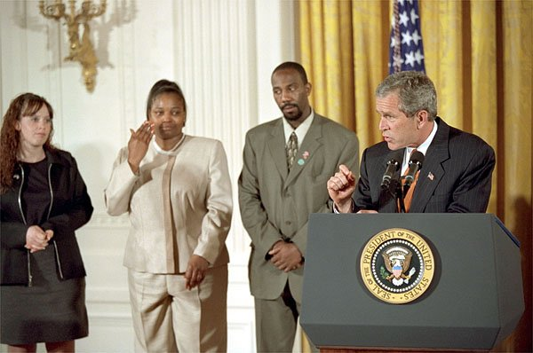 "President George W. Bush discusses welfare reform as former welfare recipient Bernadine Murphy wipes away her tears in the East Room Thursday, April 18. Also standing by the President are Tiffany Smith and Emory Bent. ""(Ms. Murphy) lived in a homeless shelter, too. She also struggled with drug abuse, and her self-esteem was, as she put it, ""nonexistent."" Bernadine enrolled in a 13-week training program, spent 11 weeks working part-time with a mentor,"" said the President, explaining that Ms. Murphy now lives in on her own and works at a law firm in Chicago. White House photo by Tina Hager."