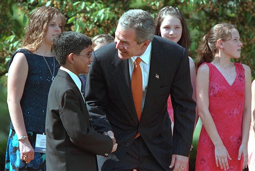"President George W. Bush greets one of the award winners during the 2002 President's Environmental Youth Awards Ceremony in The Rose Garden April 18. ""I want to thank so much the award winners for turning idealism into action; for taking a great spirit and love for our country and doing something about that spirit and love for our country."" White House photo by Paul Morse."