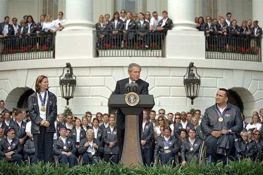 "President George W. Bush addresses visiting athletes during a ceremony honoring the efforts of the U.S. Olympic and Paralympic teams on the South Lawn Tuesday, April 23. Pictured on stage with the President is gold medalists Tristan Gale, left, and Manuel Guerra. ""It is a great honor to host our nation's Olympic and Paralympic athletes here at the White House,"" said the President ""You competed with honor, you won with humility and you made America proud."" White House photo by Tina Hager."