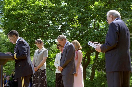 Led by Army Chaplain David Hicks, President George W. Bush prays with the family and friend of two recipients of the medal of honor during posthumous ceremony in the Rose Garden May 1, 2002. White House photo by Tina Hager.