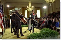 "President George W. Bush and Laura Bush listen to Pedro Fernandez perform during a reception honoring Cinco de Mayo in the East Room Friday, May 3. ""The victory we commemorate today is a source of tremendous pride to the people of Mexico, and a source of inspiration to the people of America,"" said the President in his remarks of the celebration that marks Mexico's victory over French occupying forces at the Battle of Puebla in 1862. White House photo by Susan Sterner."