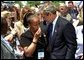 "President George W. Bush embraces a woman at the 21st Annual Peace Officers Association Memorial Service at the United States Capitol Wednesday, May 15. ""When an officer dies in the line of duty, an entire community will pause in sorrow and in admiration with the depth of feeling Americans reserve for people who protect us every day,"" said the President in his remarks to the families of fallen peace officers."