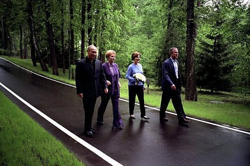 President George W. Bush and Laura Bush walk with Russian President Vladimir Putin and his wife Lyudmila on the grounds of their dacha , May 24, 2002. White House photo by Eric Draper.