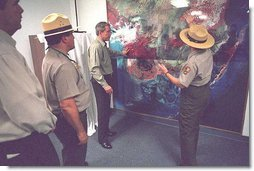 President George W. Bush looks over a topography map with national park service officer upon arriving at the Royal Palm Visitors Center at Everglades National Park, Fla., File photo. White House photo by Moreen Ishikawa.