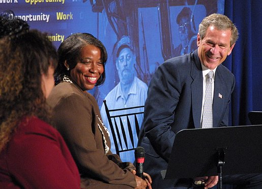 President George W. Bush laughs with participants during a conversation on welfare reform at The Church at Rock Creek in Little Rock, Arkansas on June 3, 2002. White House photo by Eric Draper.