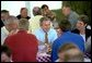 President George W. Bush sits down with families at a barbecue picnic at the 14th Annual World Pork Expo in Des Moines, Iowa. The President's Job and Growth Plan helps American families by increasing the standard deduction for married couples, raising the Child Tax Credit and eliminating the double taxation of dividends earned by stockholders White House photo by Eric Draper