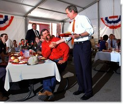 President George W. Bush greets Texas hog farmer George Fink before sitting down to eat during a barbque picnic with pork producers and their families at the World Pork Expo in Des Moines, Iowa, Friday, June 7, 2002. White House photo by Eric Draper.