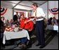 President George W. Bush greets Texas hog farmer George Fink before sitting down to eat during a barbque picnic with pork producers and their families at the World Pork Expo in Des Moines, Iowa, Friday, June 7, 2002.