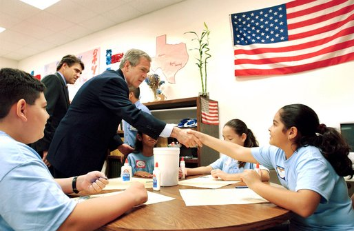 President George W. Bush visits with art students at the Association for the Advancement of Mexican Amercians Headquarters Summer Enrichment Camp in Houston, Texas, Friday, June 14. Also pictured at left, is Texas Gov. Rick Perry.