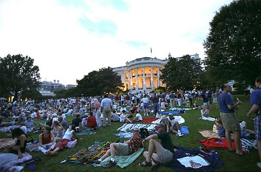 Awaiting a show of explosions of color, White House staff members and their families relax on the South Lawn Thursday, July 4, 2002. Shortly before the fireworks began, President Bush joined the party and watched the display from the Truman Balcony. Watch webcast of Fireworks on the National Mall. White House photo by Tina Hager.
