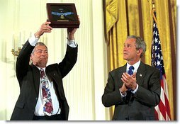 Steve Versace holds up the Medal of Honor that President George W. Bush presented to him on the behalf of his brother, Army Captain Humbert