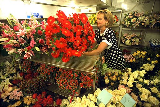 White House Florist Wendy Elsasser prepares an arrangement of red Gerbera Daises as one of the many bouquests to be used at the State Dinner for Polish President Alexander Kwasniewski tonight, July 17. White House photo by Tina Hager.
