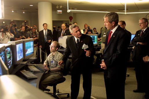 President George W. Bush listens to Hermann Grunder, Director of the Argonne National Laboratory, during a tour of the research facilities with Homeland Security Director Tom Ridge, Secretary of Energy Spencer Abraham and Speaker of the House of Representatives Dennis Hastert, R-IL., in Argonne, IL., July 22. Sponsored by the Dept. of Energy and operated by the University of Chicago, the laboratory is combating terrorism through innovative projects such as detectors for neutrons, biological and chemical agents and developing an emergency response system that coordinates various technologies. White House photo by Paul Morse.