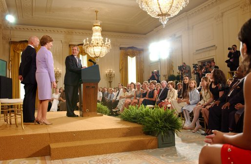 President George W. Bush watches the new Public Service Announcement that encourage adoption with Actor Bruce Willis and Mrs. Bush in the East Room July 23, 2002. White House photo by Tina Hager.