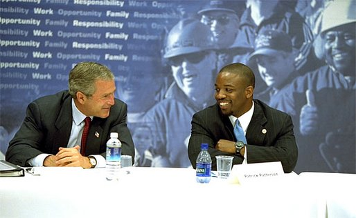 "President George W. Bush talks with Patrick Patterson during a roundtable discussion on welfare reform in Charleston, S.C., Monday, July 29. ""I believe that compassionate welfare reform must move forward, to strengthen work, to insist upon work as one of the benchmarks for success, because I believe work increases somebody's self worth and dignity,"" said President Bush of the reauthorization vote on the 1996 welfare reform bill. White House photo by Paul Morse."