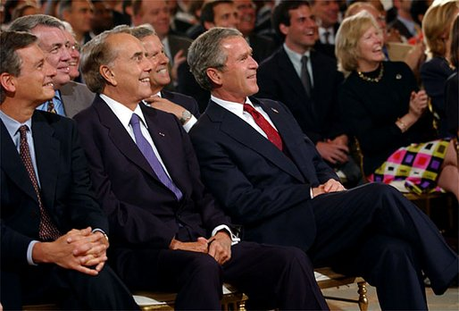 President George W. Bush sits with former Senator Bob Dole, center, and Mayor Stephen Goldsmith and watches the new public service announcement for the USA Freedom Corps in the East Room July 30.