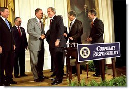 "President George W. Bush shakes hands with Sen. Mike Oxley, R-MD, during the signing of the ceremony of the Sarbanes-Oxley Act in the East Room, July 30. ""This new law sends very clear messages that all concerned must heed. This law says to every dishonest corporate leader: you will be exposed and punished; the era of low standards and false profits is over; no boardroom in America is above or beyond the law,"" said the President in his remarks. White House photo by Eric Draper."