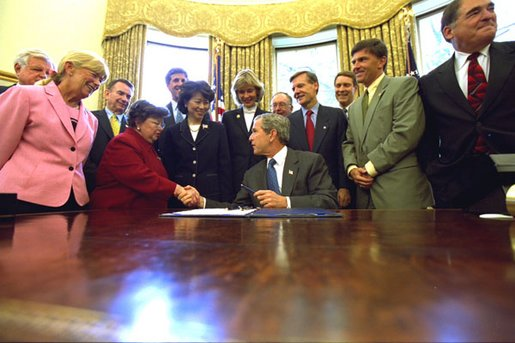 President George W. Bush talks with invited guests Thursday, Aug.1, after signing the Nurse Reinvestment Act of 2002 in the Oval Office. The legislation will create financial assistance programs for nursing students and support the nursing profession through public service announcements. White House photo by Tina Hager.