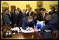 President Bush signs a team jersey for the U.S. Soccer Team in the Oval Office Friday, August 2, 2002. White House photo by Eric Draper.