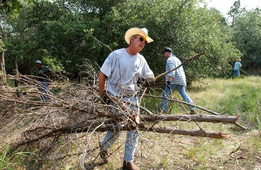 President George W. Bush clears cedar at his ranch in Crawford, Texas, Friday, Aug. 9, 2002. White House photo by Eric Draper.