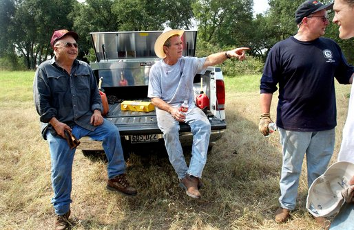 President George W. Bush takes a break from cedar clearing at his ranch in Crawford, Texas, Friday, Aug. 9, 2002. Also pictured are, from left, friend Ken Englebrecht, Deputy Chief of Staff Joe Hagin and White House staffer Reed Dickens. White House photo by Eric Draper.
