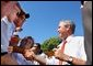 President George W. Bush greets the audience after speaking at the Iowa State Fair Fairgrounds, Wednesday, Aug. 14, 2002.
